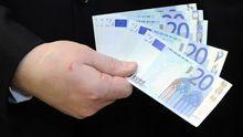 Ein Mann hält Euro-Scheine in der Hand