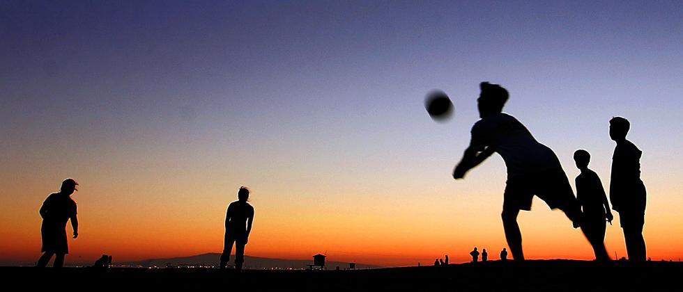 Junge Leute spielen Volleyball zusammen