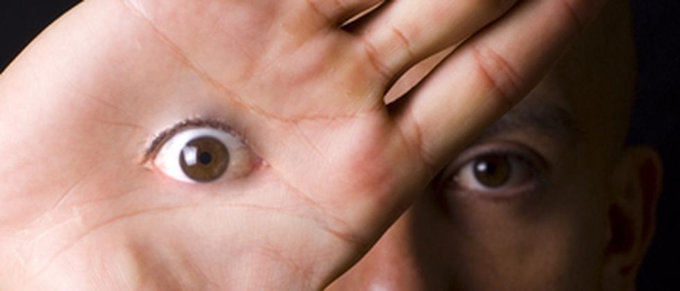 Fotomontage: Ein Mann hat ein Auge in der Handinnenfläche