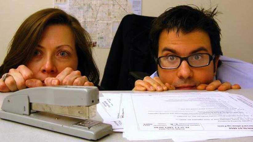 Zwei Mitarbeiter lugen hinter dem Schreibtisch hervor