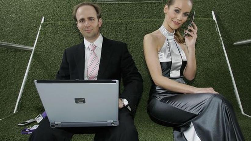 Ein Mann und eine Frau mit Handy und Computer