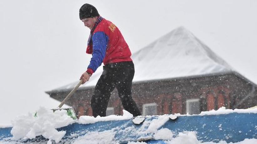 Ein Arbeiter schippt Schnee von einem Dach