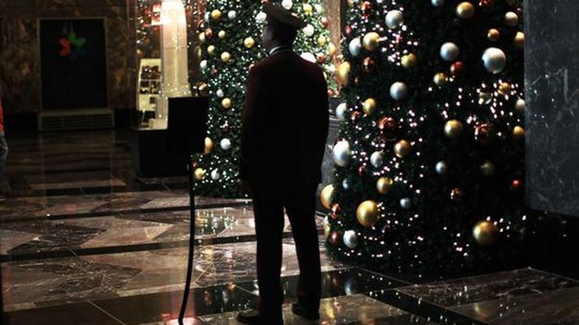 Ein Mann steht neben einem Weihnachtsbaum
