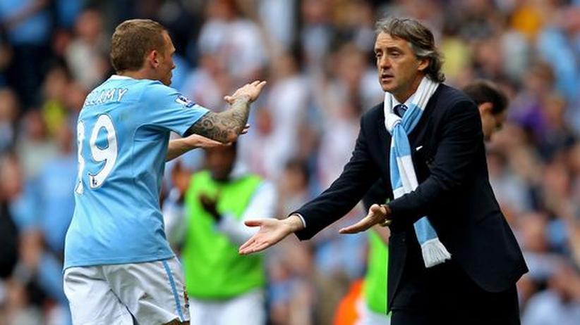 Der Spieler Craig Bellamy von Manchester City freut sich mit seinem Manager Roberto Mancini über ein gewonnenes Spiel: Ein guter Chef hat sein Team so organisiert, dass er vom Spielfeldrand Anweisungen gibt