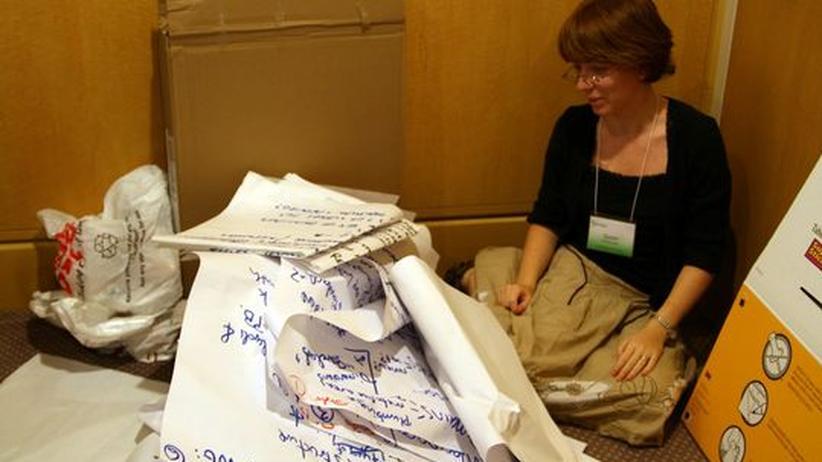 Eine Mitarbeiterin sitzt im Papierchaos aus zerknüllten Flipcharts
