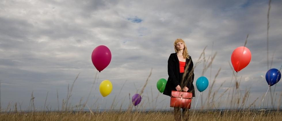 Frau mit Luftballons in Herbstlandschaft