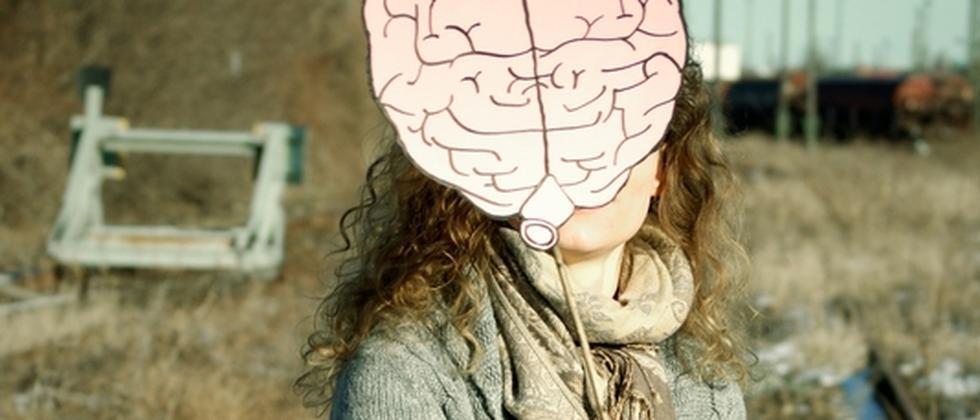 Frau mit einem Gehirn aus Pappe in der Hand