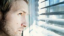 Ein Mann schaut sorgevoll aus dem Fenster.