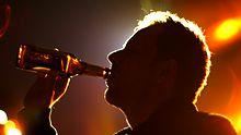 Ein Mann trinkt aus einer Bierflasche.