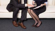 Ein Kollege tätschelt einer Frau das Knie.