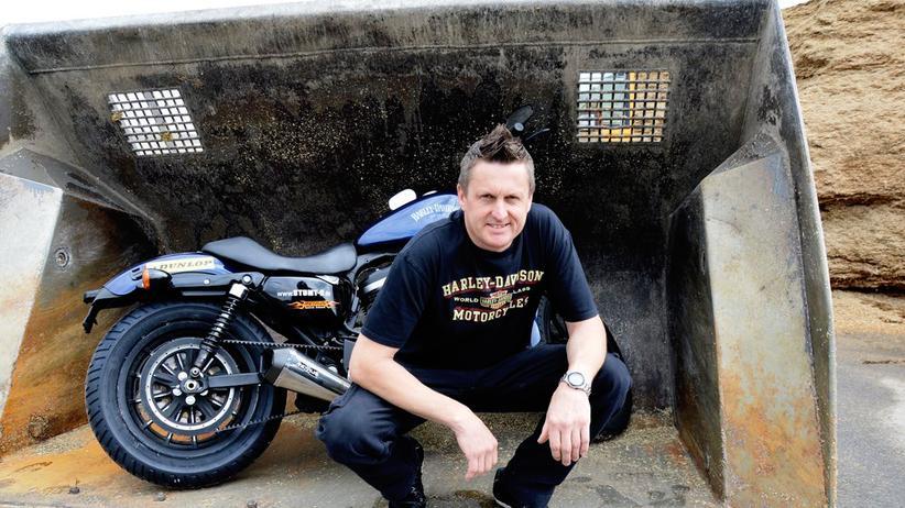 Landleben: Bauer Rainer Schwarz posiert mit einer seiner Harleys in der Schaufel eines Radladers vor der Maissilage seiner Biogasanlage.