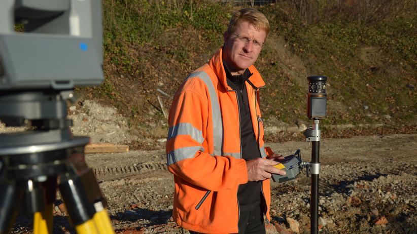 Geodät: Gunther Schmidt mit Tachymeter und elektronischem Feldrechner: Der Geodät vermisst eine Fläche, auf der ein Gebäude geplant wird. Den Rechner hat er in der Hand, das Tachymeter ist das Gerät mit den gelben Standbeinen.