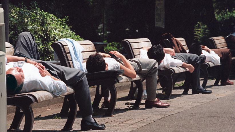 Arbeitspausen: Japanische Angestellte halten ein Nickerchen auf Parkbänken im Hibiya-Park in Tokio.
