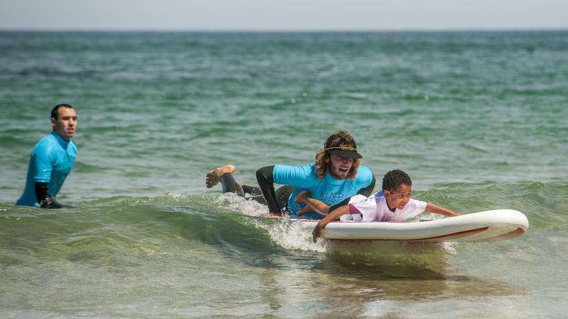 Surflehrer bringen Kindern das Wellen reiten am Strand von San Sebastian in Spanien bei.