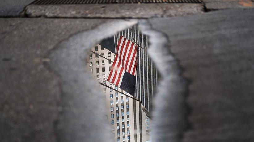 Thomas Weimann: Eine amerikanische Flagge spiegelt sich in einer Pfütze.