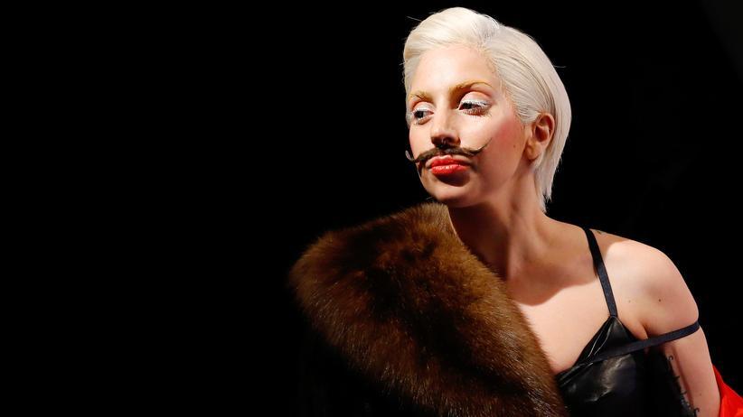 Lady Gaga in Berlin: Lady Gaga präsentiert sich in Berlin schlicht mit schwarzem Schnurrbart.
