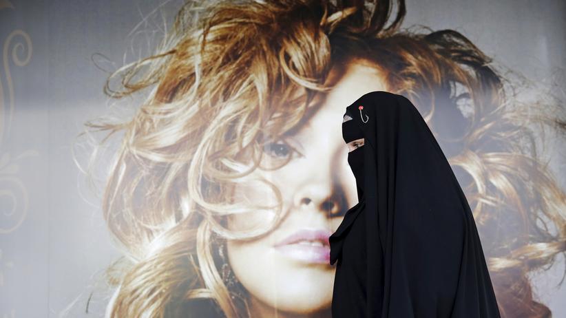 Frauenfeindlichkeit: Wer nicht mit Fremden spricht, kann auch nichts lernen: Auf diesem Bild aus São Paulo sehen wir die Muslima Gisele Marie vor einer Plakatwand. Sie ist Frontfrau der Heavy-Metal-Band Spectrus.