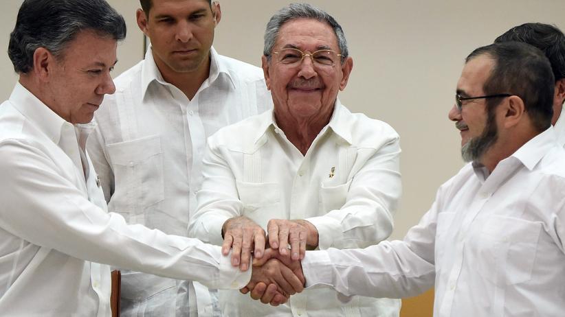 Der Handschlag zwischen dem kolumbianischen Präsidenten Juan Manuel Santos (li.) und FARC-Anführer Timoschenko (re.), besiegelt durch Kubas Präsident Raúl Castro.