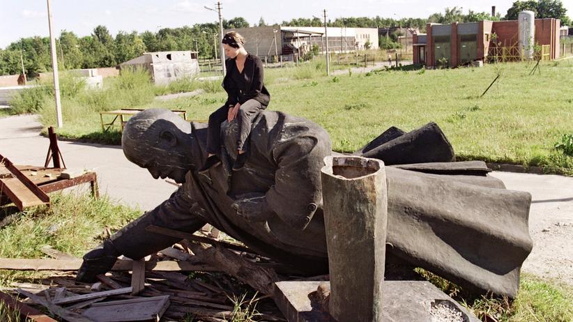 Eine junge Litauerin sitzt im September 1991 auf einem umgestürzten Lenin-Denkmal.