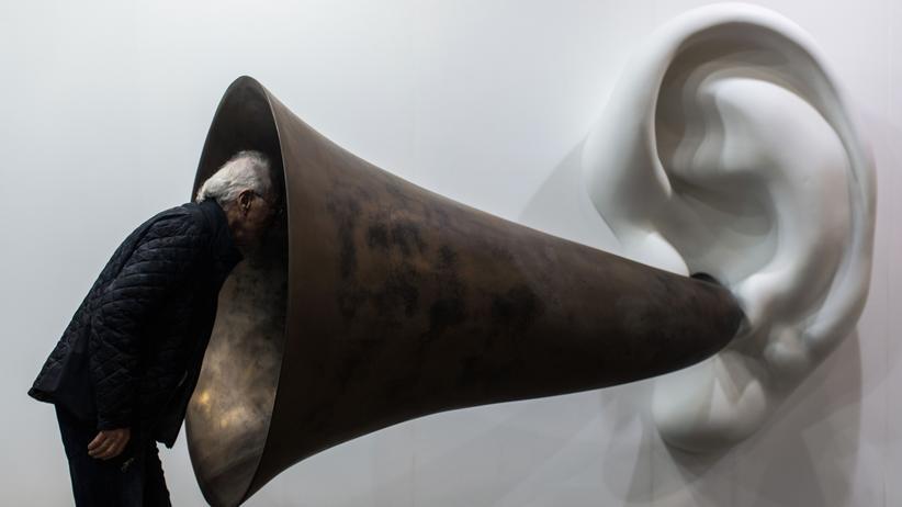 Artsy: Ein Messegast inspiziert auf der Art Basel die Kunst.