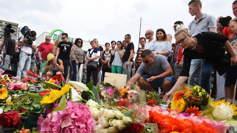 Amoklauf in München: Trauer zeigen und Trauernde filmen: Nahe des Olympia-Einkaufszentrums in München legen Menschen Blumen nieder.