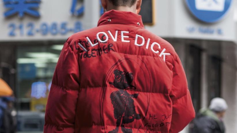 Künstler: Ein junger Mensch, auf dessen Jacke I LOVE DICK steht, ist auf dem Prospekt der Berlin Biennale zu sehen.