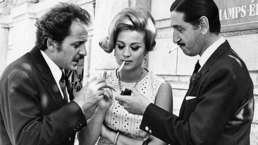 Diskriminierung: Zwei Herren bieten der italienischen Schauspielerin Liana Orfei Feuer an. 1960 wie heute, das ist einfach gutes Benehmen.
