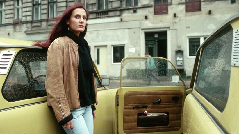 Gleichberechtigung: Eine junge Frau in Ostdeutschland 1990 neben zwei Trabis