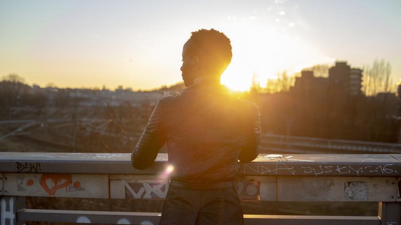 Integration: Silhouette einer jungen Frau im abendlichen Gegenlicht auf einer Brücke