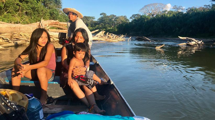 Amazonas: Txana, ein Schamane vom Volk der Huni Kuin, steuert das Boot. Das Mädchen links ist die ältere Tochter von Batani.