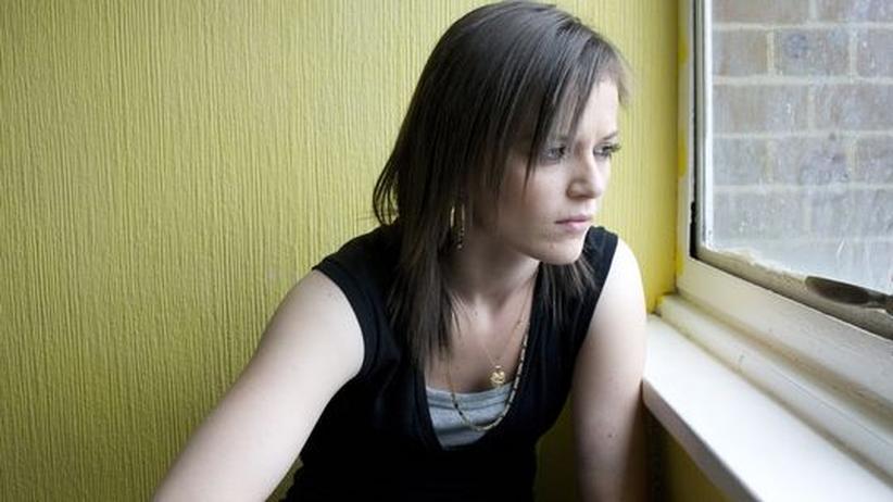 braunhaariges Mädchen schaut aus dem Fenster, sie trägt ein schwarzes Oberteil und eine goldene Kette, sowie Ohrringe