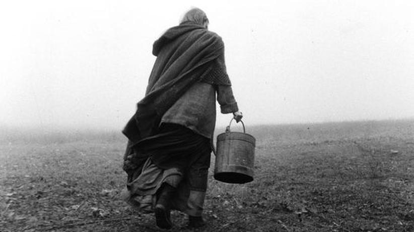 """Film """"Das Turiner Pferd"""": Der tägliche Gang zum Brunnen: Erika Bók kämpft sich durch den unheilvoll heulenden Wind vor ihrer Steinhütte."""