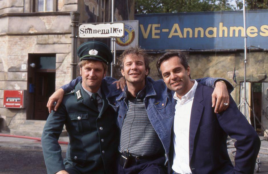 """Die DDR war seit zehn Jahren Geschichte, da wurde sie wieder aufgebaut für """"Sonnenallee"""" (Regie: Leander Haußmann, Mitte, Produzenten: Detlev Buck – der auch mitspielt –, links, und Claus Boje). Hier hatte eine Kulisse aus 18 Fassaden Premieren, die fortan Berliner Straße hieß."""