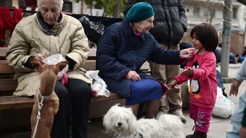 Fremdsprache: Eine ältere Frau in Athen spricht mit einem geflüchteten Mädchen.
