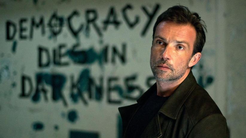 """""""Polizeiruf"""" Frankfurt/Oder: Adam Raczek (Lucas Gregorowicz) vor dem Schriftzug """"Democracy dies in Darkness"""""""