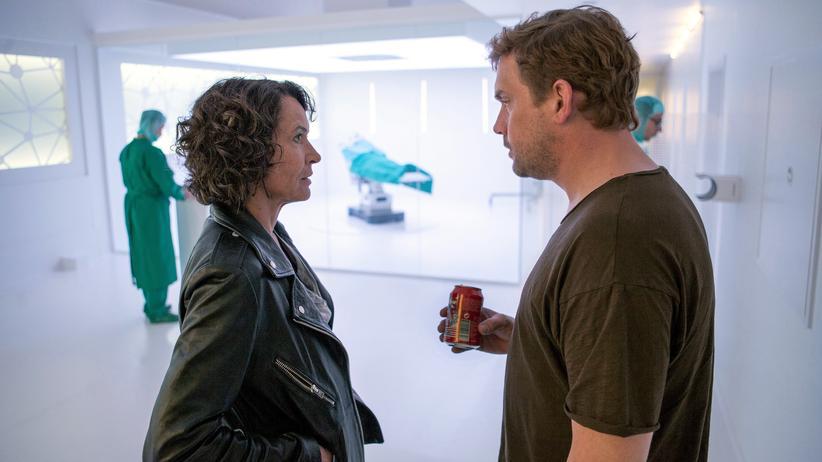 """""""Tatort"""" Ludwigshafen: Professor Bordauer (Sebastian Bezzel, re.) zeigt Lena Odenthal (Ulrike Folkerts) seinen Operationssaal, in dem ein Roboter ferngesteuerte Operationen durchführt."""