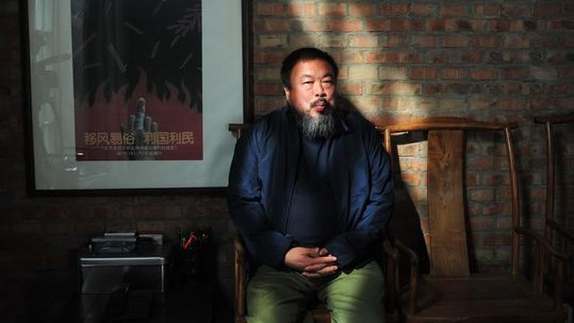 Der chinesische Künstler Ai Weiwei in seinem Haus im Künstlerviertel in der Vorstadt Pekings auf einer Bank