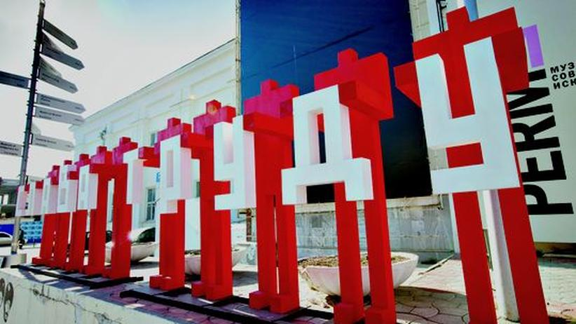 """Rote Männchen mit dem Schriftzug """"Ruhm der Arbeit"""""""