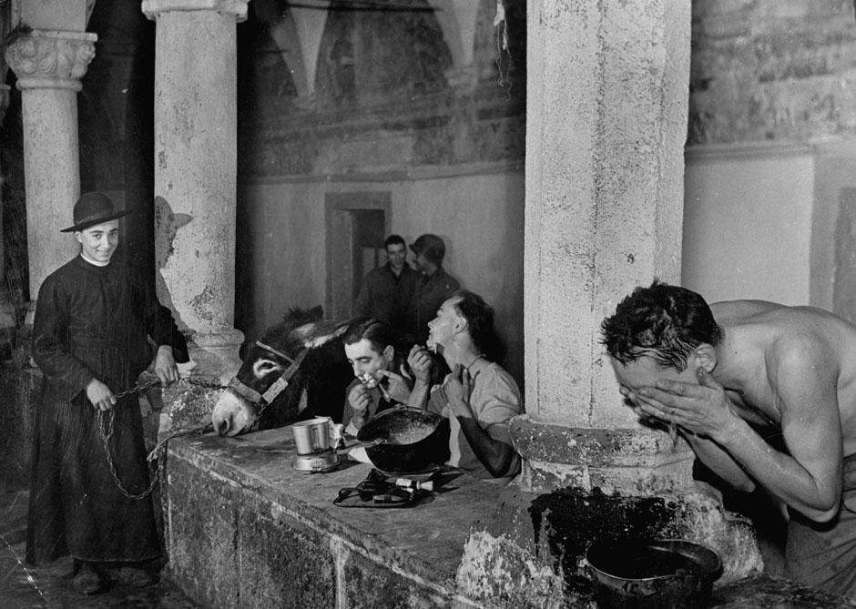 Ein Priester beobachtet US-amerikanische Soldaten bei ihrer morgendlichen Toilette in einem mittelalterlichen Kloster in Italien, 1943.