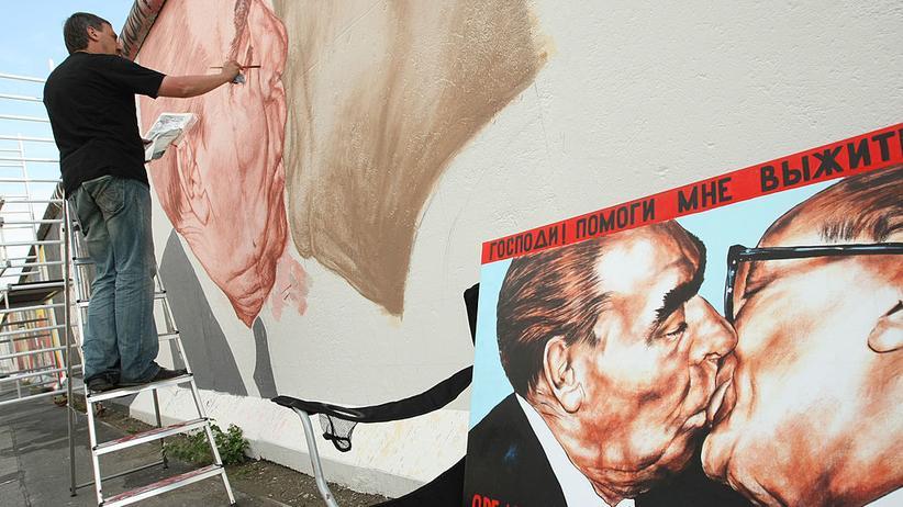 """East Side Gallery: """"Bruderkuss"""" mit neuem Anstrich: der Künstler Dmitri Vrubel 2009 während der Renovierungsarbeiten an der East Side Gallery."""
