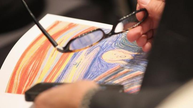 """Kunstfälschung: Ein Interessent blättert im Sotheby's Katalog zur Versteigerung des Gemäldes """"Der Schrei"""" von Edvard Munch (Archivbild)."""