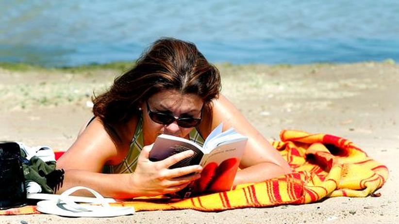 Literaturtipps: Ein Strand, ein Buch: Diese Frau erholt sich mit Lektüre am Lake Michigan.