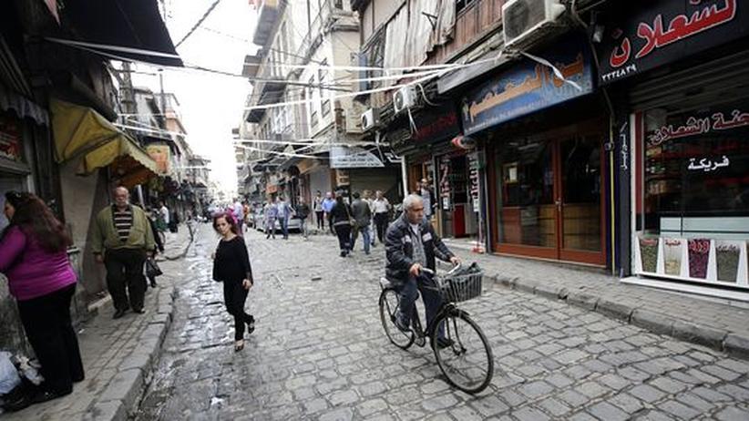 Ein Mann fährt auf seinem Fahrrad durch eine Straße in Damaskus.