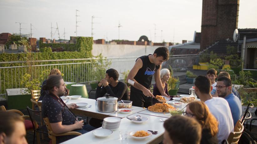 Ahmad Mansour und Aladin El-Mafaalani: Migranten und einheimische Berliner während eines gemeinschaftlichen Abendessens auf dem Dach des Sharehaus Refugio in Berlin, August 2015