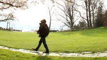 Ein Mann spaziert durch einen Park in Zürich.