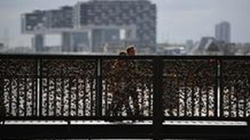 Zwei Passanten überqueren die Hohenzollernbrücke in Köln