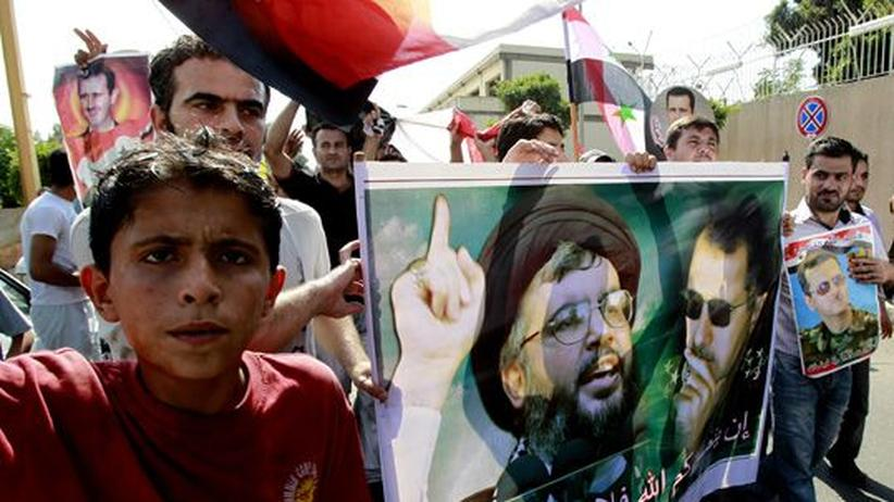 Hisbollah: Hisbollah-Anhänger mit einem Bild ihres Anführers Hassan Nassrallah (l.) und des syrischen Präsidenten Baschar al-Assad