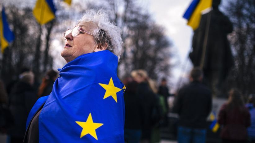 Europa: Eine Frau, eingewickelt in eine Flagge der EU, in der ostukrainischen Stadt Luhansk