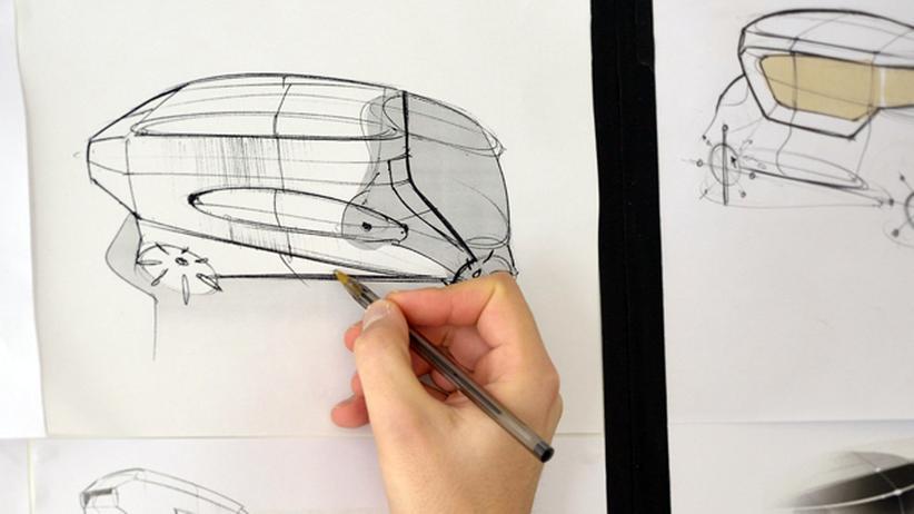Autodesign-Student Kenan Haliloglou zeichnet an einer Skizze.
