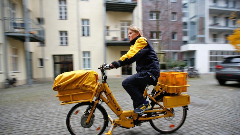 Eine Postbotin auf einem Elektrofahrrad